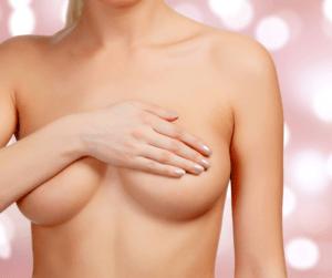 Naga kobieta zasłania ręką piersi.