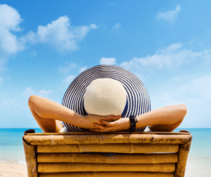 Kobieta w kapeluszu opala się na leżaku na plaży.