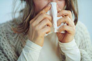 Chora na grypę kobieta wydmuchuje nos w chusteczkę higieniczną.