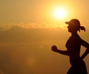 kobieta biegnie na tle zachodu słońca