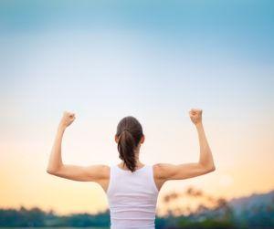 Kobieta stoi tyłem i napina mięśnie obu ramion