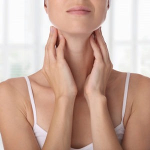 Kobieta dotyka swojej szyi