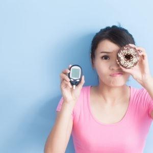 Kobieta trzyma pączka i glukometr