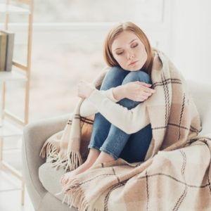 Kobieta siedzi przykryta kocem