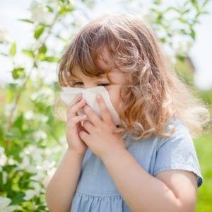 Dziewczynka wydmuchuje nos na tle kwitnących roślin