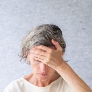 Kobieta trzyma dłoń na czole