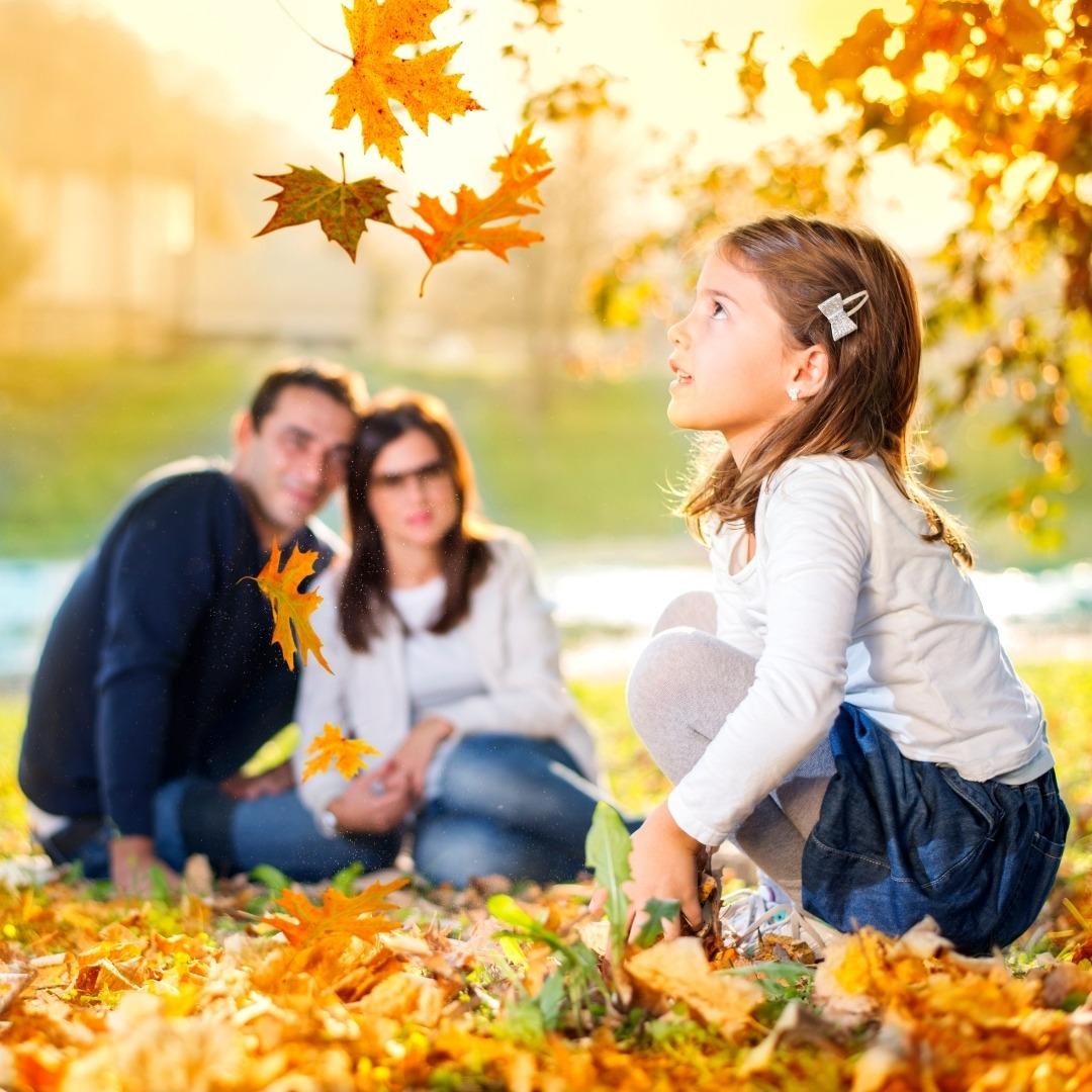 Dziewczynka i rodzice bawią się jesiennymi liśćmi